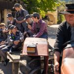 A farmer driving a tractor carrying people on a wagon